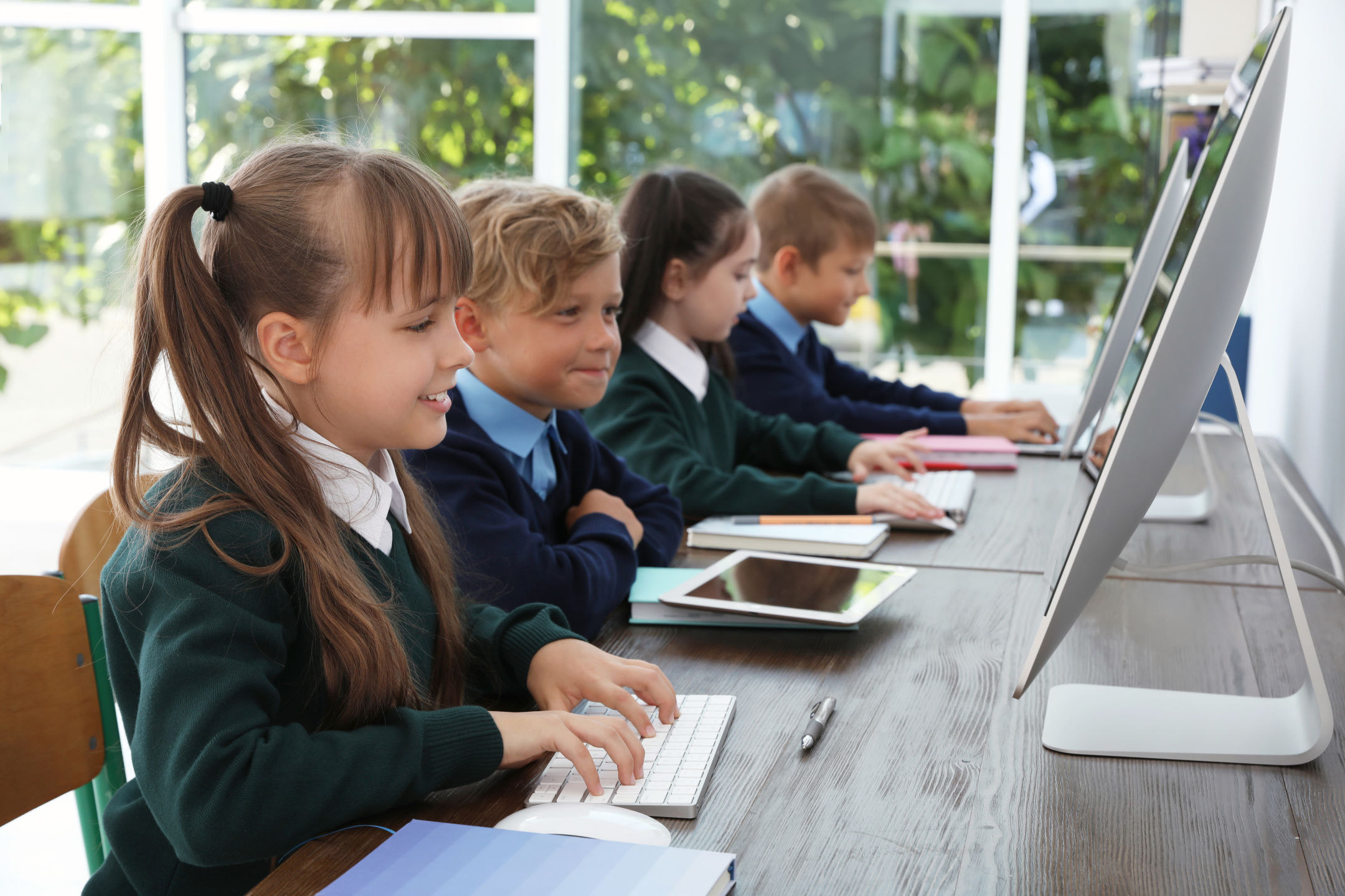 A group of pupils paired up at computers.