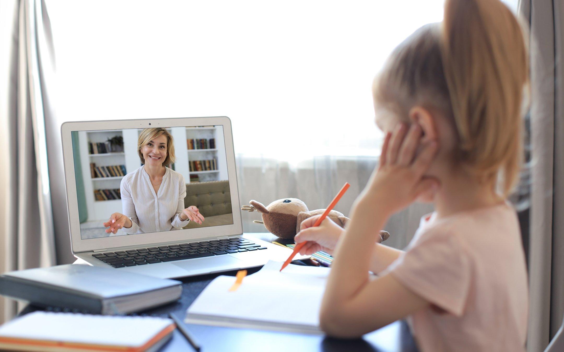 Girl watching teacher on laptop screen