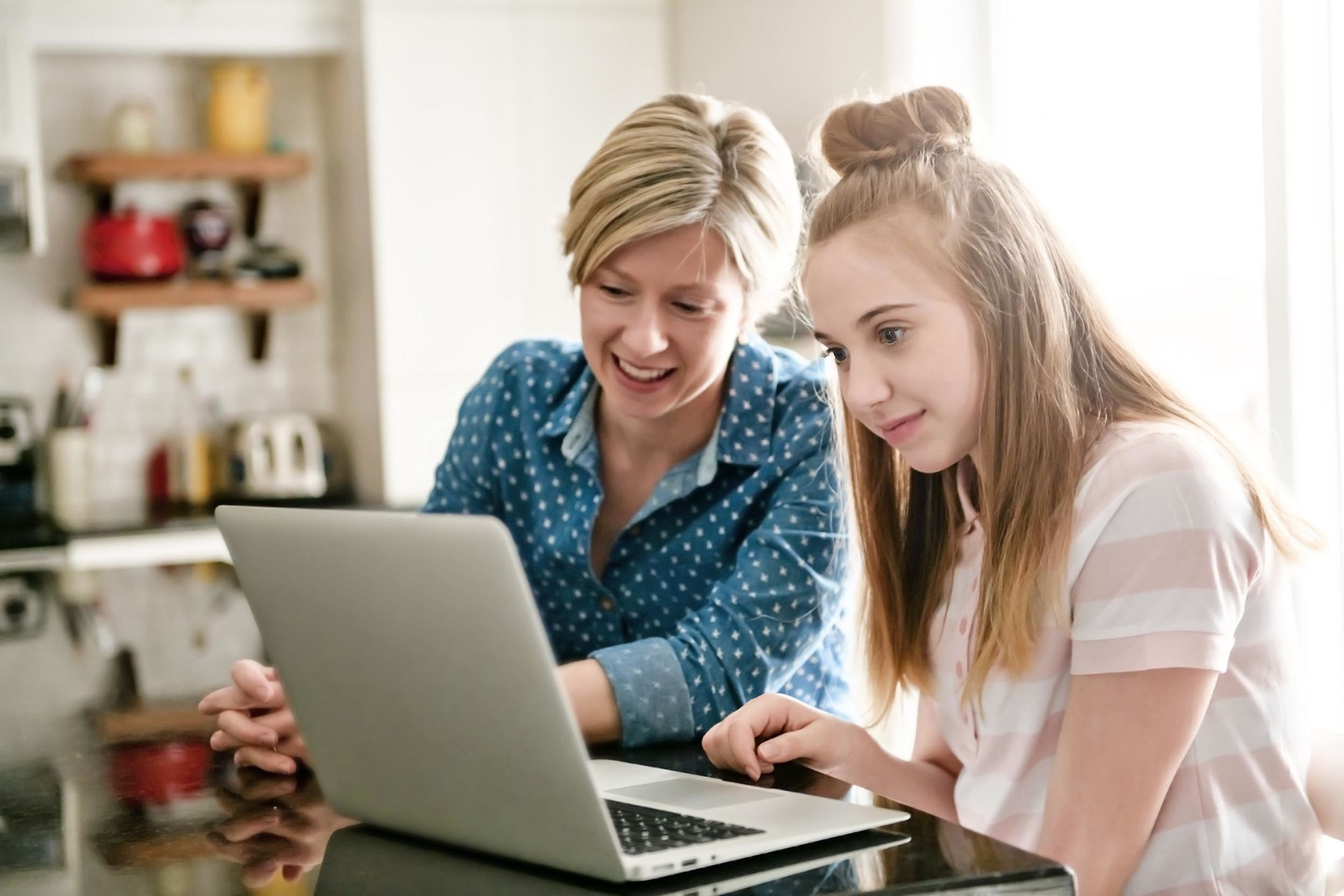 A parent and daughter working together on a laptop.