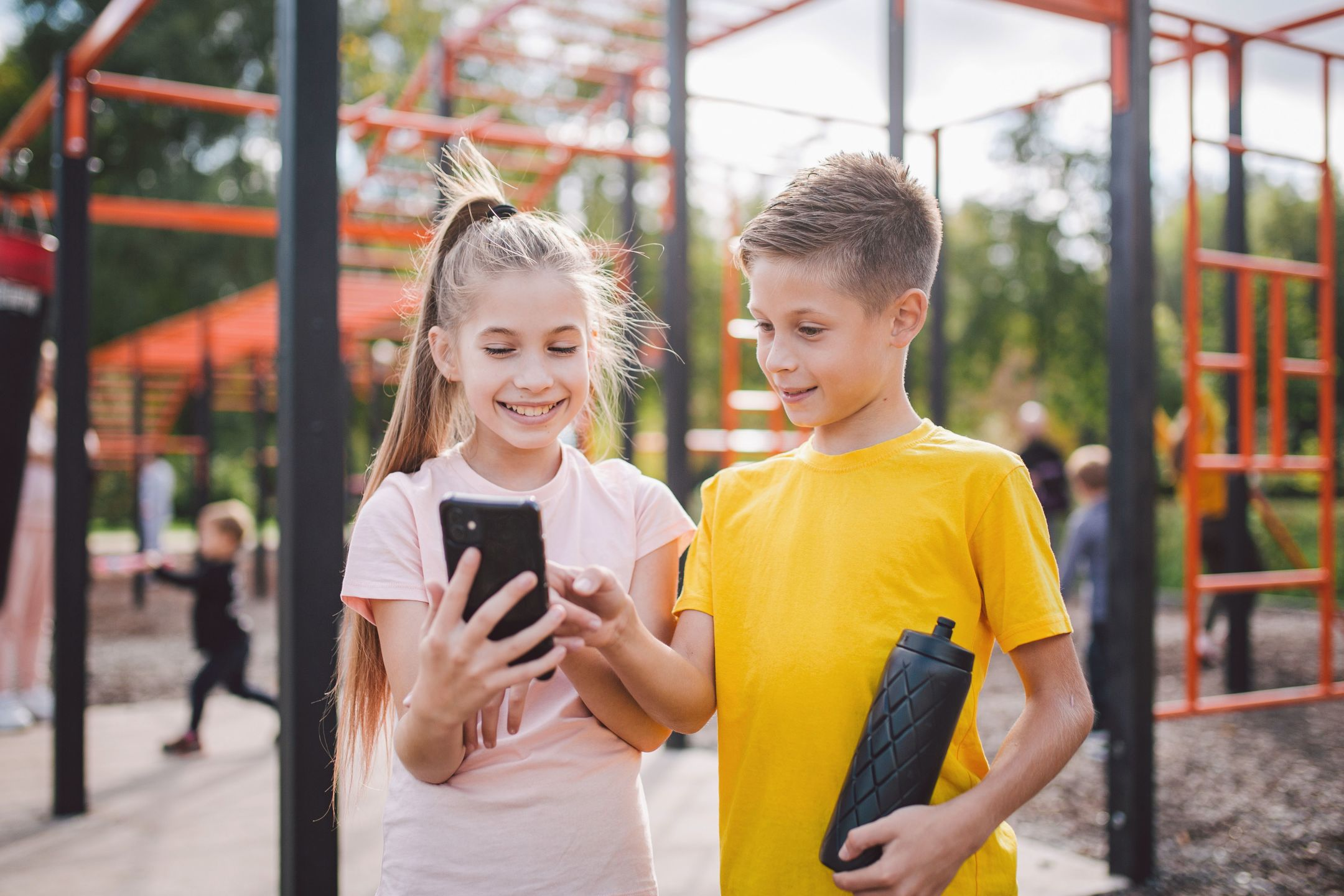 Two children taking break from playing in the park to look at at Oak on their mobile.