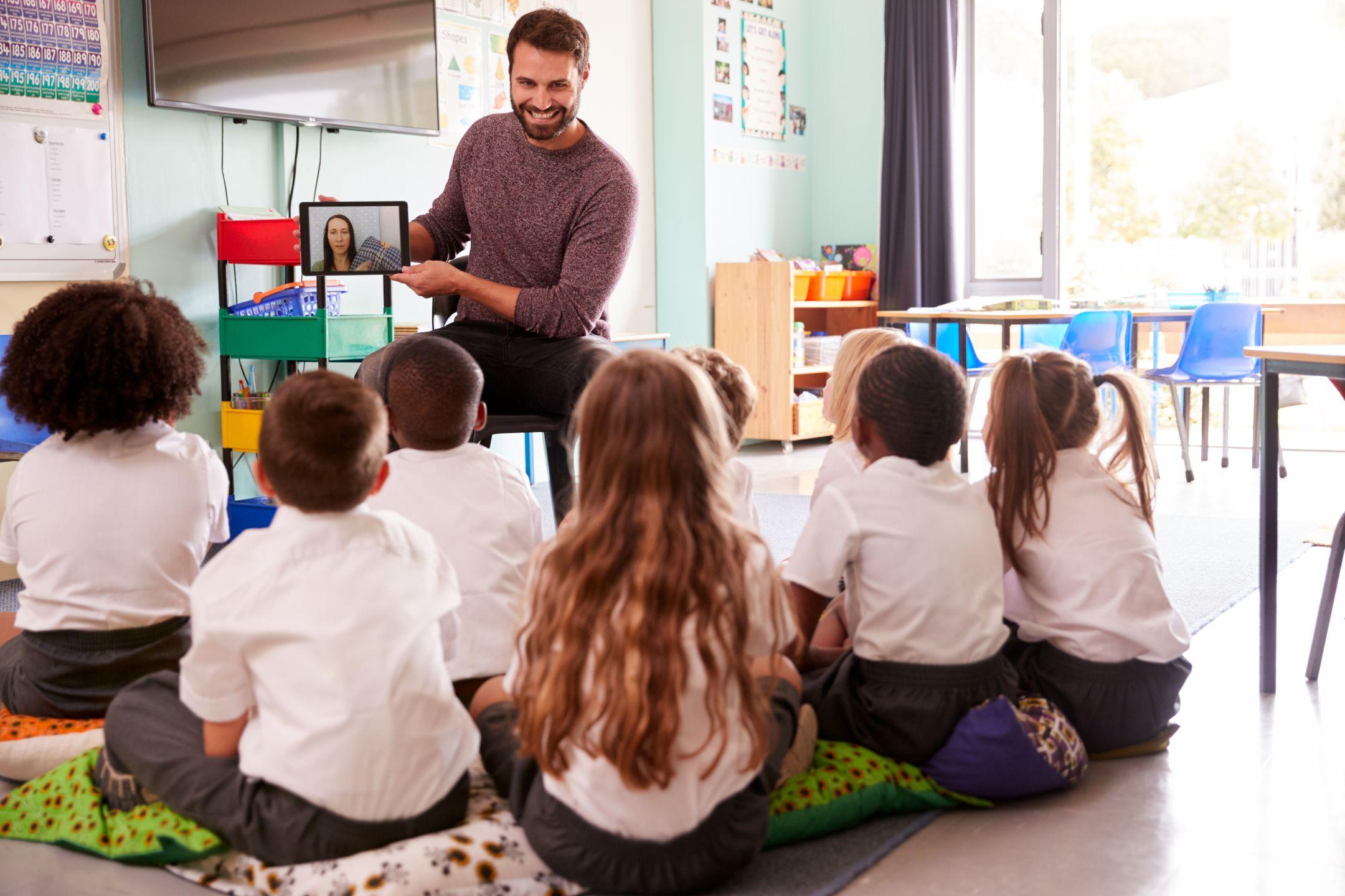 A teacher referring an Oak video to his class using a tablet.