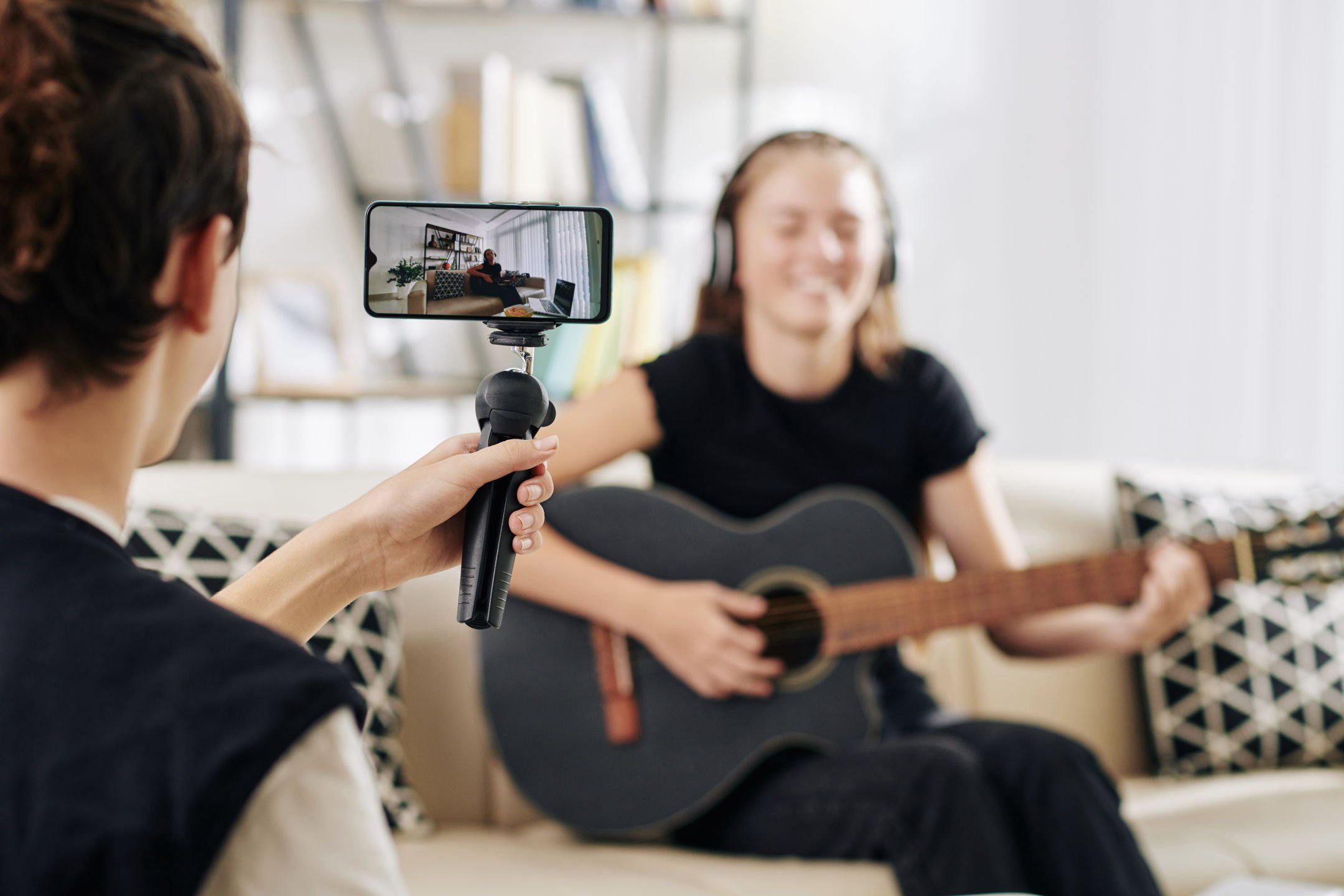 A boy recording a girl playing the guitar at home.